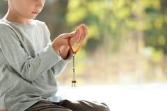 Liten muslimsk pojke med misbaha som inomhus ber, closeup royaltyfri foto
