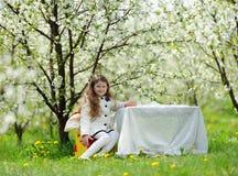 Liten nätt flicka i den gröna trädgården Arkivfoto
