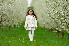 Liten nätt flicka i den gröna trädgården Arkivfoton