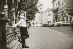 Liten nätt flicka som går på stadsgatan arkivfoto