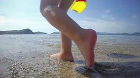 Liten naken babygirl som går på havskusten på den soliga sommardagen och med en hink av vatten behandla som ett barn havet lager videofilmer