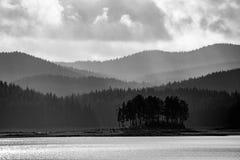 Liten naturlig ö med i lager bergbakgrund arkivbilder