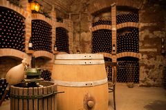Liten och gammal vinkällare med många fulla flaskor och kaggen royaltyfri fotografi