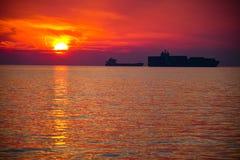 Liten och stor kontur för behållaretankfartygskepp som parkeras i en fjärd med en härlig solnedgånghimmel fotografering för bildbyråer
