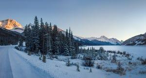 Liten och tom vinterväg, med lite skogen och den stora fryste sjön under solnedgång i härliga berg, Banff nationalpark, C arkivbild