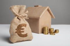 Liten påse med pengar- och eurotecknet Bunt av mynt och husmodellen Inteckna den finansiella egenskapen Stigande hyra Hus och myn royaltyfria foton