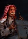 """Liten Petra, Jordanien†""""Juni 20, 2017: Gammal beduinman eller arabman i den traditionella dräkten som spelar hans musikinstrume Arkivfoto"""