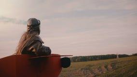 Liten pilot- flicka som kör i rolig plan dräkt med färgrök i hand på fantastisk ultrarapid för höstsolnedgångfält arkivfilmer