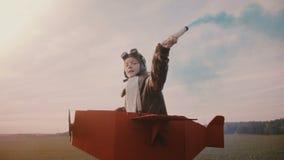 Liten pilot- flickaspring, bärande rolig pappnivådräkt med blå färgrök på höstsolnedgångultrarapid lager videofilmer