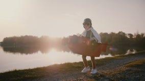 Liten pilot- pojke som kör i rolig flygplandräkt med exponeringsglas på episk ultrarapid för panorama för flod för solnedgångpane arkivfilmer