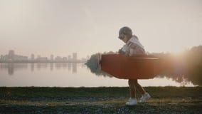 Liten pilot- pojke som startar till den inkörda roliga pappnivån på panorama för flod för solnedgångpanelljusstad och att ha roli stock video