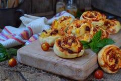Liten pizza med mozzarellaost, skinka, basilika, körsbärsröda tomater Bullar av jästdeg på träbakgrund lycklig timme hemlagat b arkivfoton