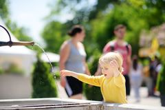 Liten pojke för blont hår som spelar med stadsspringbrunnen på solig sommardag arkivbild