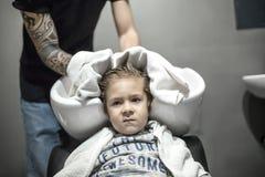 Liten pojke i frisersalong royaltyfri foto