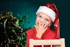 Liten pojke i näsa för santa hattval Arkivbild