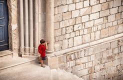 Liten pojke i rött nederlag bak pelare royaltyfri bild