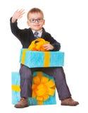 Liten pojke i spectecles med den stora presenten Fotografering för Bildbyråer