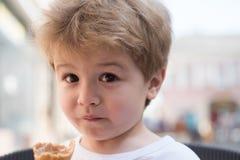 Liten pojke med stilfull frisyr Litet barn med kort blont hår Äta för litet barn royaltyfri fotografi
