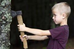 Liten pojke med trumf för träd för tung gammal järnyxa bitande i skog på sommardag Utomhus- aktiviteter och läkarundersökningarbe Fotografering för Bildbyråer