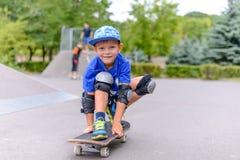 Liten pojke på hans skateboard som grinar på kameran royaltyfri foto