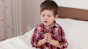 Liten pojke som ber, unge som säger bönen, innan att gå att bädda ned, stark tro i hjärta, pojke som ber till guden arkivfilmer