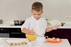 Liten pojke som gör bakningen i köket Royaltyfri Bild