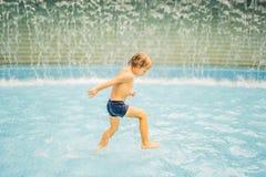 Liten pojke som har rolig spring i simbassäng arkivfoton