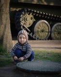 Liten pojke som huka sig ned bredvid behållare Royaltyfria Bilder