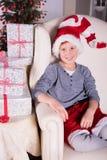 Liten pojke som mycket är upphetsad om gåvorna för jul Royaltyfria Bilder