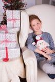 Liten pojke som mycket är upphetsad om gåvorna för jul Royaltyfri Fotografi