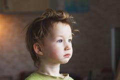 Liten pojke som sitter nära fönster och tänker om något Han har härligt stort hår behandla som ett barn gulligt fotografering för bildbyråer