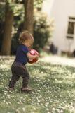 Liten pojke som spelar med en boll Arkivfoton