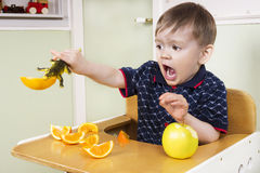 Liten pojke som spelar med hans frukt Arkivbilder