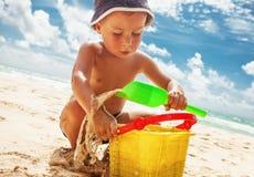 Liten pojke som spelar med leksaker på stranden Arkivbild