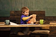 Liten pojke som spelar med nallebjörnen under skolaavbrott Gullig unge med hans favorit- leksak Bildande lek i dagis arkivfoton