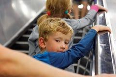 Liten pojke som tillbaka ser på rulltrappan Arkivbild