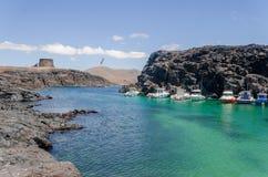 Liten port med fartygandbluevatten Fuerteventura Cotillo arkivfoto
