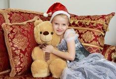 Liten prinsessa på helgdagsaftonen för ` s för nytt år med en nallebjörn Arkivfoto