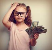 Liten professor i ögonexponeringsglas som skrapar huvudet, hållande pengar Arkivbild