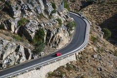 Liten röd bil på vägen i bergen Arkivfoto