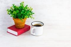 Liten röd bok, kaffekopp och grön blomma i lantlig keramisk kruka Vit träbakgrund, kopieringsutrymme Arkivbild