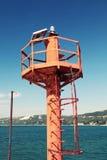 Liten röd fyrpol på kusten av havet royaltyfri bild