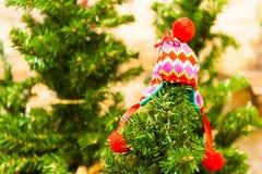 Liten röd hatt för barn` som s hänger på den ljusa julgranen - grön bakgrund Arkivfoton