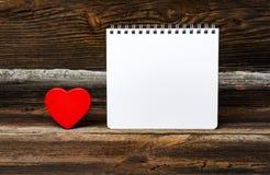 Liten röd hjärta med notepaden Arkivfoto