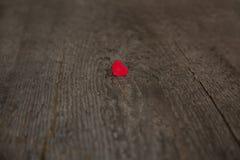 Liten röd hjärta på ett gammalt träbräde för valentindagnärbild royaltyfri foto