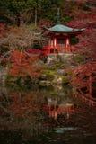 Liten röd japansk relikskrin med dess reflexion i dammet royaltyfri fotografi