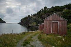 Liten röd koja längs en ojämn kustlinje på flasklilla viken i Newfoundland arkivfoton