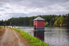 Liten röd koja som byggs på en flod och förbinds till en bro med att förbluffa naturligt landskap fotografering för bildbyråer