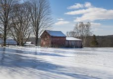 Liten röd ladugård i ett iskallt vinterlandskap royaltyfria foton
