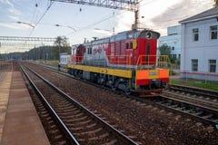 Liten röd lokomotiv som kyler på sidorailpath royaltyfri foto